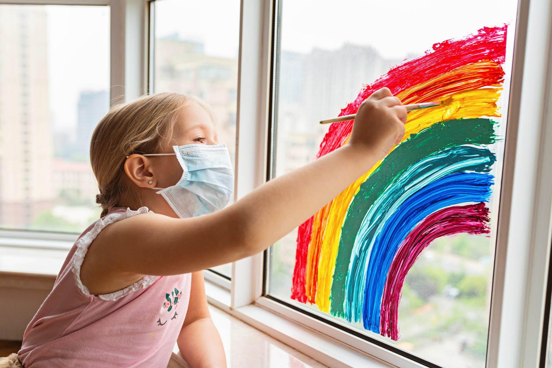 Menina de máscara a pintar na janela um Arco-Íris